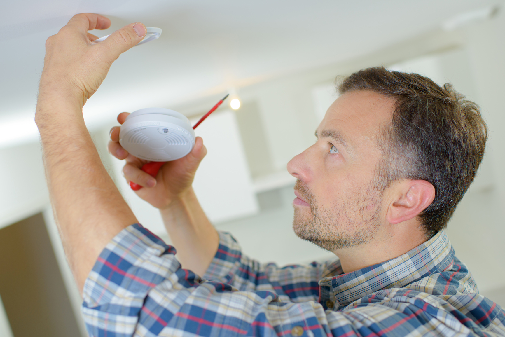 Electrician fitting a fire alarm
